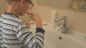 De gelukkige jongen wast zijn handen met zeep en borstelt zijn tanden in badkamers Het kind houdt water en hygiëne van procedures stock footage