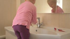 De gelukkige jongen wast zijn handen met zeep en borstelt zijn tanden in badkamers Het kind houdt water en hygiëne van procedures stock videobeelden