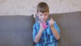 De gelukkige jongen zet een roze slijm bij zijn handzitting op de bus en het spelen stock footage