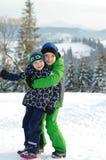 De gelukkige jongens die op de winter spelen lopen in aard Kinderen die en pret in de winterpark springen hebben royalty-vrije stock afbeeldingen