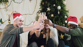 De gelukkige jongeren die wijn drinken tijdens viert Nieuwjaar of Kerstavond, die grote tijd in het ontspannen van huis hebben stock video