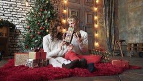 De gelukkige jongeren geeft elkaar giften door de open haard dichtbij de Kerstboom stock videobeelden