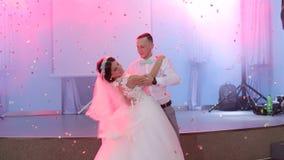De gelukkige jonggehuwden dansen de eerste dans in het restaurant stock video