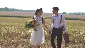 De gelukkige jonggehuwden houden handen en lopen op het de lentegebied De uitstekende geklede bruid houdt het boeket stock footage