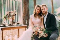 De gelukkige jonggehuwden kijken op een fotograaf De man en de vrouw in feestelijke kleren zitten op de stenen dichtbij de huweli Stock Afbeeldingen