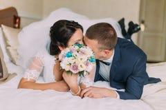 De gelukkige jonggehuwden leggen op bed in hotelruimte na huwelijksviering en aandeelkus Royalty-vrije Stock Foto