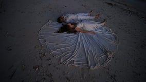 De gelukkige jonggehuwden liggen op het zand tijdens zonsondergang op de huwelijkskleding van de bruid Het originele idee van fil stock footage