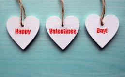 De gelukkige kaart van de de daggroet van Valentijnskaarten Decoratieve witte houten harten op een blauwe houten achtergrond Stock Fotografie