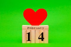 De gelukkige kaart van de Valentijnskaartendag met rood document hart en houten kalender Stock Foto's