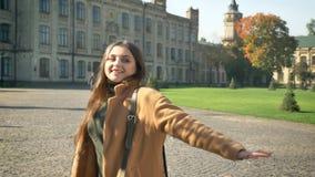 De gelukkige Kaukasische vrouw bevindt zich en geniet van sunshines op haar gezicht, aardig weer, de herfst vibes, toevallige mod stock video