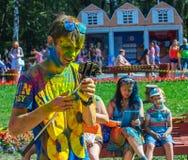 De gelukkige kerel bekijkt smartphone Het festival van kleuren Holi Royalty-vrije Stock Fotografie