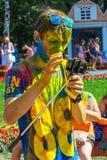 De gelukkige kerel bekijkt smartphone Het festival van kleuren Holi Royalty-vrije Stock Afbeeldingen