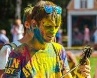 De gelukkige kerel bekijkt smartphone Het festival van kleuren Holi Stock Foto