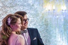 De gelukkige kerel en het meisje in avond of huwelijkskleding kijken één manier samen op een lichte achtergrond Stock Foto