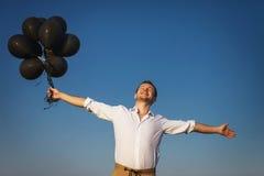 De gelukkige kerel met zwarte ballons bereikt voor de hemel Stock Fotografie