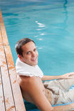 De gelukkige kerel ontspant binnen de pool stock afbeelding