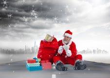 De gelukkige Kerstman die met muntnota's naast 3D Kerstmisgiften zitten Stock Foto's