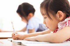 De gelukkige kinderen bestuderen in het klaslokaal stock fotografie