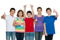 De gelukkige kinderen houden hun duimen tegen Royalty-vrije Stock Foto