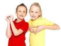 De gelukkige kinderen met een teken van hart vormen Stock Foto's