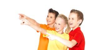 De gelukkige kinderen richten weg door vinger op iets. Stock Afbeelding