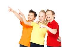 De gelukkige kinderen richten weg door vinger op iets. Stock Foto's