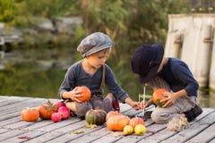 De gelukkige kinderen schilderen kleine Halloween-pompoenen Royalty-vrije Stock Afbeeldingen