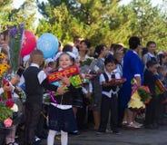 De gelukkige kinderen schreven in de eerste rang met giften in hand met leraren en leerlingen op de school de plechtige heerser i Stock Foto
