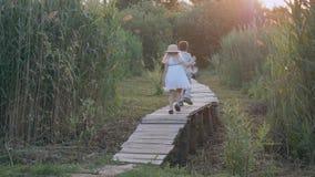 De gelukkige kinderenspelen, weinig jongen en meisjesspel lopen en lopen op houten brug onder groen hoog riet de achterstand in stock videobeelden