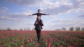 De gelukkige kinderjaren, Duitsers-mens met glimlachende jong geitjejongen spreidden wapens aan zijzitting op schoudersgang over  stock footage