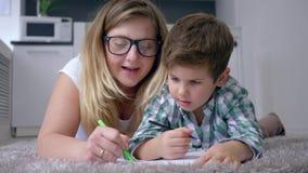 De gelukkige kinderjaren, mamma met jongen trekken met gekleurde tellers op wit blad thuis liggend op vloer in vakantie stock footage
