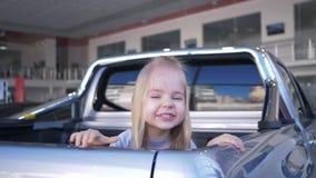 De gelukkige kinderjaren, meisje spelen huid - en - zoeken en lach in boomstamauto in verkoopcentrum stock video