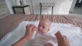 De gelukkige kinderjaren, moeder houden handen van weinig dochter en het spelen met haar die op camera op bed liggen stock videobeelden