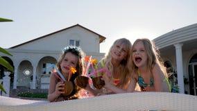 De gelukkige kinderjaren, verwende kinderen met gekleurde cocktails op opblaasbare matras, meisjes in zwempak hebben dichtbij pre stock videobeelden