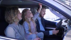 De gelukkige klanten in autowinkel, glimlachende familie met weinig dochter kiest de golvende sleutel van het familievoertuig en  stock video