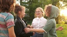 De gelukkige klasgenoten koesteren terwijl het lopen in het park, schoolvriendschap, terug naar school stock video
