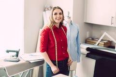 De gelukkige kleermakersvrouw met ledenpop met het meten van lijn in het atelier geniet van haar werk en zaken royalty-vrije stock afbeelding