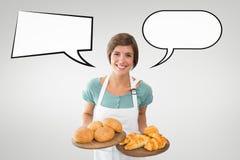 De gelukkige kleine bedrijfseigenaarvrouw met toespraak borrelt houdend gebakjes tegen grijze achtergrond Royalty-vrije Stock Foto