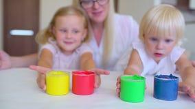 De gelukkige kleuren van familieverven Gelukkige kleine childs die kleurrijke kleur handsprint op het Witboek maken Een weinig le stock footage