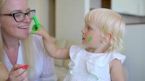 De gelukkige kleuren van familieverven Moeder en dochter die pret en verf hebben elkaar ` s op gezichten thuis Familiegrappen, Fa stock videobeelden