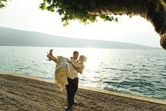 De gelukkige knappe bruid van de bruidegomholding in zijn wapens op strand bij sunse Royalty-vrije Stock Afbeeldingen