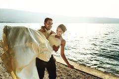 De gelukkige knappe bruid van de bruidegomholding in zijn wapens op strand bij sunse Royalty-vrije Stock Foto's