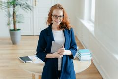De gelukkige knappe vrouwelijke beambte geniet de online bankieren van dienst, controleert saldo op aanrakingsstootkussen, leest  royalty-vrije stock afbeeldingen