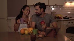 De gelukkige leden van kleine familie zit bij lijst Meisjesdranken van kop De kerel eet appel Er is tablet en busket met stock video