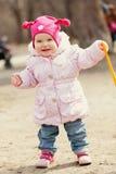 De gelukkige leuke gangen van het babymeisje in de lentepark Stock Fotografie