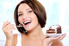 De gelukkige leuke jonge vrouw eet een cake Stock Foto
