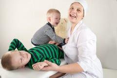 De gelukkige leuke jongens die met stethoscoop in artsenbureau spelen, koesterend pluchestuk speelgoed dragen en glimlachend bij  Royalty-vrije Stock Afbeelding