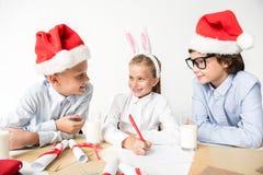 De gelukkige leuke kinderen maken Kerstmisgroeten royalty-vrije stock fotografie