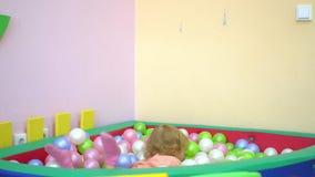 De gelukkige leuke peuter die van het babymeisje aan multi gekleurde balpool vallen peuter stock videobeelden