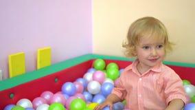De gelukkige leuke peuter die van het babymeisje en in multi gekleurde balpool glimlachen spelen peuter stock footage